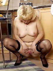 Mature blondie plays with corn at kitchen
